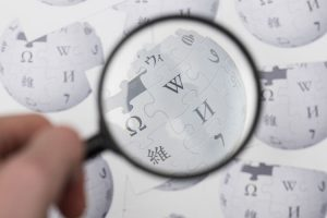Wikipedia logo printed onto paper. Wikipedia is a free online encyclopedia.