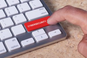 Man pressed keyboard button with cybersecurity word