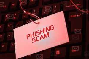 digital screen over the keyboard showing PHISHING SCAM