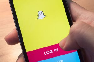 mobile phone held in one hand showing its screen with Snapchat application.