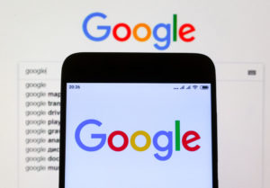 Google sign seen displayed on smartphone and the laptop display.