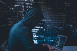 Anonymous hacker in a black hoody with laptop in front of a code background with binary streams cyber security concept