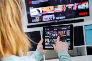 Woman Holding a touch pad and switching channels on France Netflix HomePage. with TV set on background.