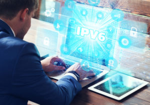 Business, technology, internet and networking concept. Young businessman working on his laptop in the office, select the text IPV6 on the virtual display.