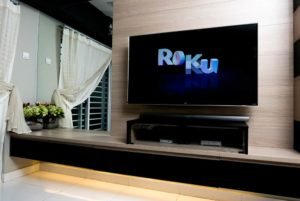 Modern lifestyle with LG Android TV to stay connected & browsing media using favourite Apps. TV display Roku logo over black background.